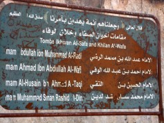 """Sign outside Jabal Mashadin Masyaf, Syria. Jabal Mashad is believed to hold the tombs of Imam Muhammad ibn Isma'il and the three Isma'ili Imams who succeeded him : Imam 'Abdullah ibn Muhammad al-Radi [Imam Wafi Ahmad], Imam Ahmad ibn 'Abdullah al-Wafi [Imam Taqi Muhammad], and Imam al-Husayn ibn Ahmad al-Taqi [Imam Radi al-Din 'Abdullah]. The first line of the sign reads: 'God, the Exalted said: """"We made them Imams guiding by Our Command"""" [Qur'an: 21:73 & 32:24], God speaks the truth.' The second line is translated below it."""