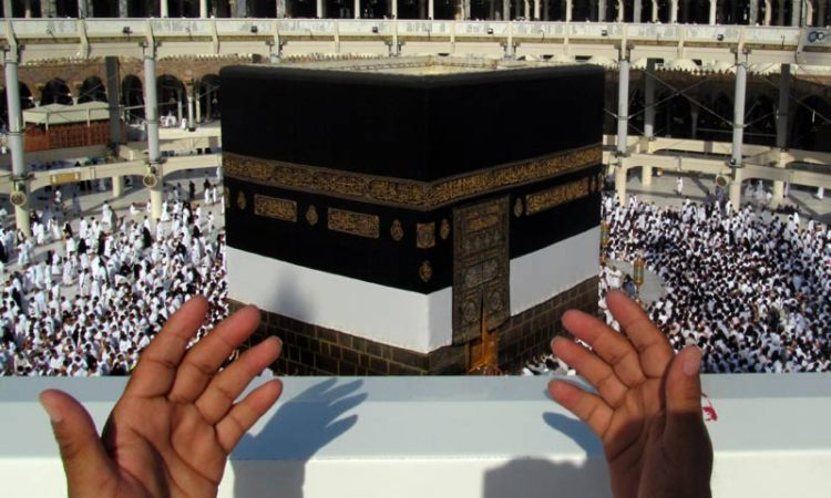 A Hajj pilgrim praying and supplicating towards the Ka'bah.
