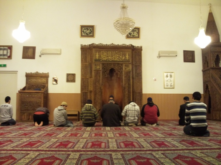 Muslim praying in the masjid while facing the mihrab.