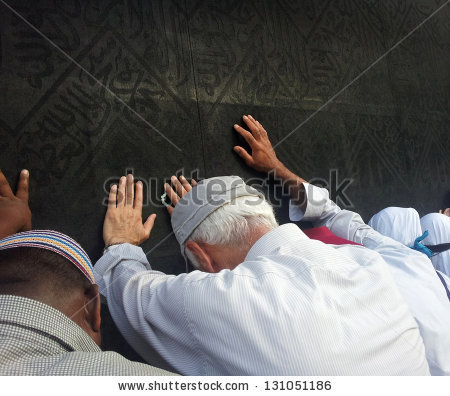 A pilgrim touches and bows before the Ka'bah during the Hajj.