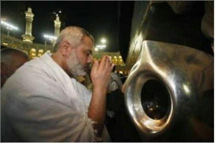 A Hajj pilgrim supplicates and prays before the Black Stone.
